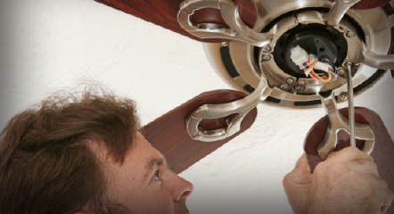 A service man working on the wiring of a ceiling fan.