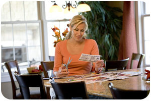 A woman sitting at a table clipping coupons