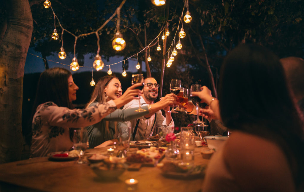 Friends toasting with wine and beer at rustic dinner party
